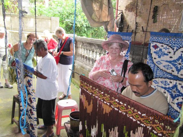 Men arrange and dye threads for ikat weavers.