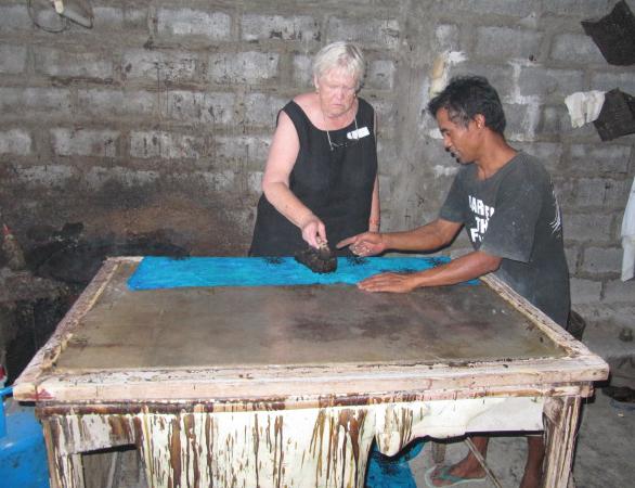 A tour guest tries tjapping rayon batik.