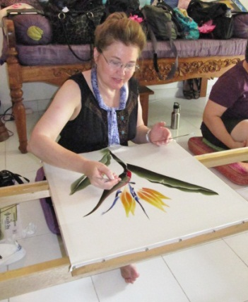 "Tjanting wax outlines stop dyes from spreading, allowing us to ""color inside the lines."" Here a tour guests paints on silk that has the outline of a flower drawn in wax with a tjanting tool."