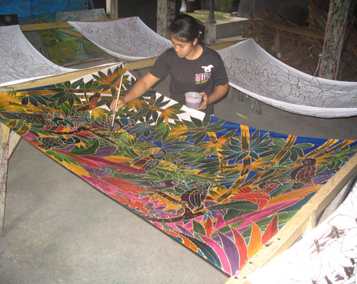A woman paints a sarong.