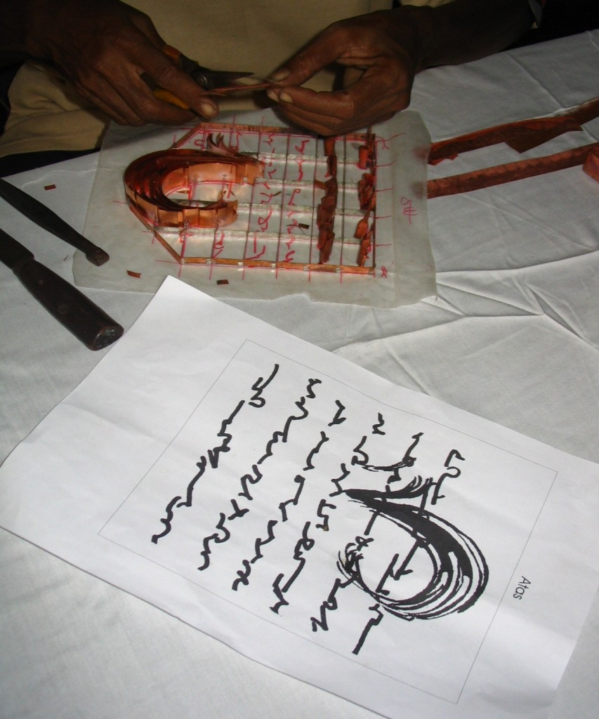 The artist's sketch is traced in red ink onto wax paper and marked with a grid. There is a corresponding grid on the copper frame and the tjap maker duplicates the artwork as he bends and snips the copper strips. The bits and pieces are then tapped into the copper frame that is later welded to a heavy steel frame. The maximum size for a tjap is 14 inches square. It can take up to one week to complete a tjap depending on complexity of design.