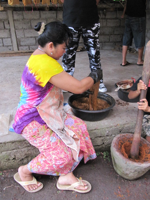 Dyeing silk threads for ikat weaving. The rust-colored mash on the right is the root scraping of the morinda tree. It will later be wrung by hand into water to form a dye bath. The dyer is dipping silk threads in the morinda dye. Photo is of Master dyer/teacher/Balinese textile historian Ida Ayu Ngurah Puniari.