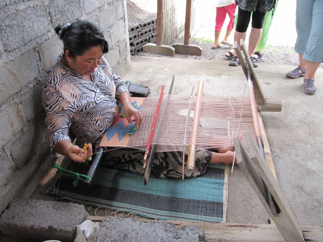 D'Ayu demonstrates supplementary weft weaving where the silk threads float above the warp.