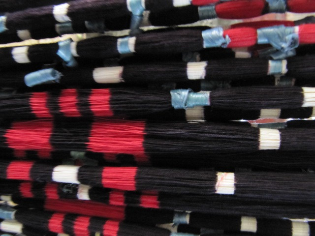 Threads are wrapped in plastic raffia (blue here) to seal in the color. The raffia is later removed to reveal the color beneath.