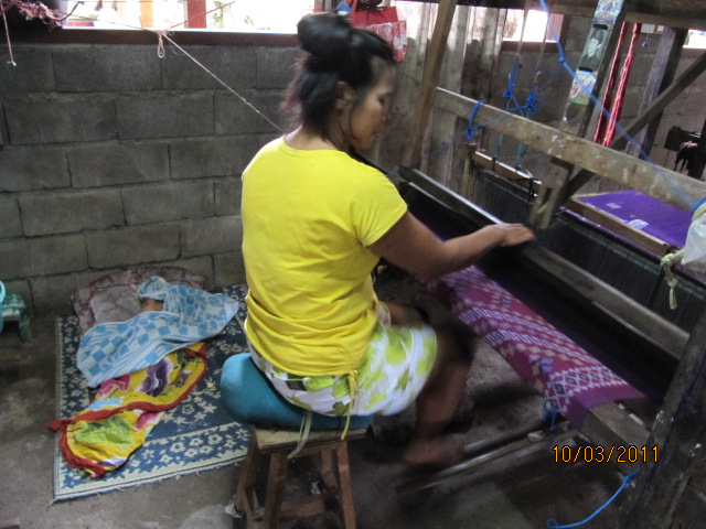In this typical weaving cooperative, women can drop-in, use the equipment and be paid by the piece. This young mother weaves as her baby girl sleeps beside her. Friendships are formed between the women as they learn this skill.